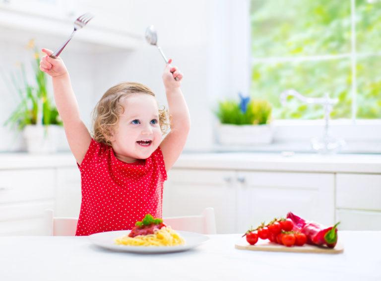 Funny toddler girl eating spaghetti in white kitchen